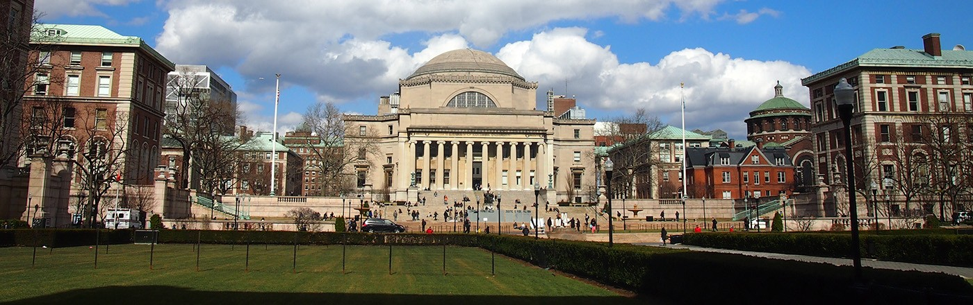 Low Memorial Library, with its grand steps and granite dome, sits at the center of Columbia's Morningside campus, as large cumulus clouds float across a bright, blue sky